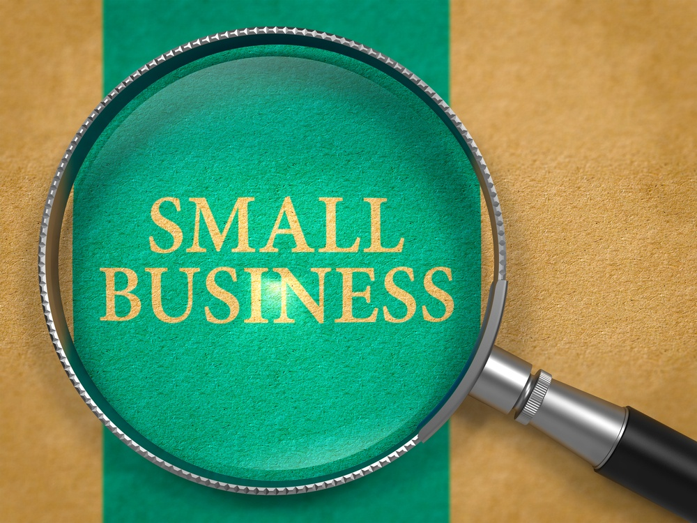 Small Business Concept through Magnifier on Old Paper with Blue Vertical Line Background..jpeg